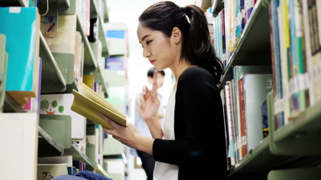 Asian students smiling and reading a book in library. video
