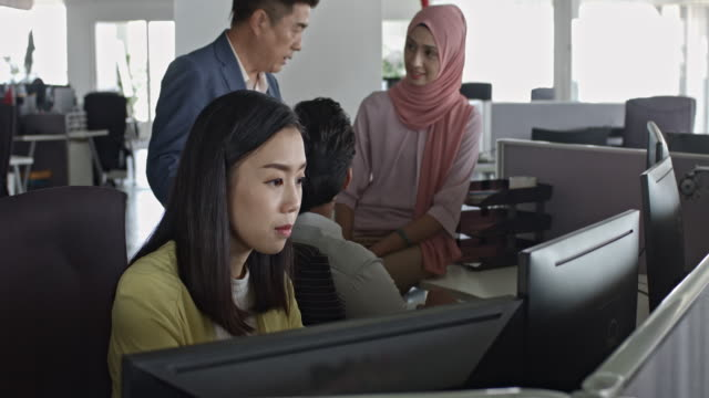 asian supervisor checking his colleagues at office desk - office cubicle stock videos & royalty-free footage