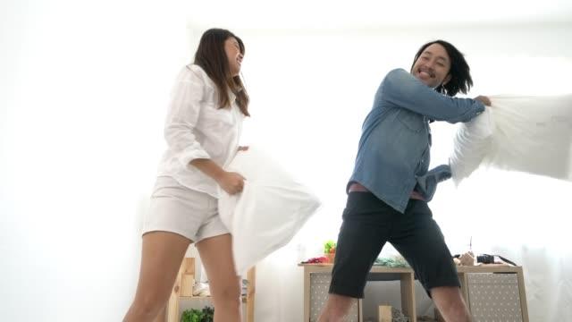 stockvideo's en b-roll-footage met aziatische sweet marry paar kussengevecht voor leuke slaapkamer achtergrond - couple fighting home
