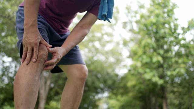 vídeos de stock e filmes b-roll de asian tan skin male having painful knee injury during jogging exercise inside the park with trees on the background, body condition knee pain, joint ligament problem, out door exercise knee ache - dor