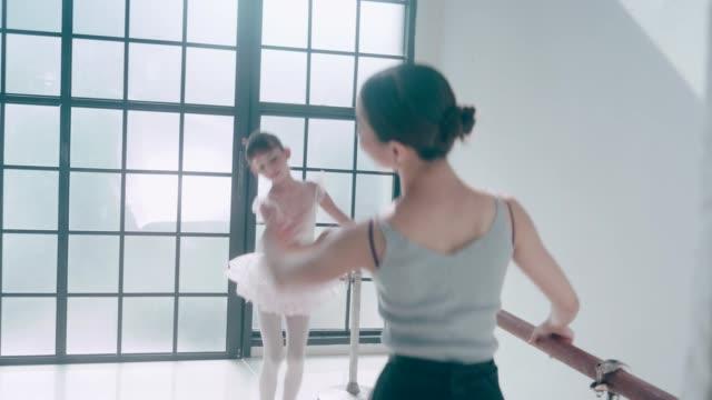 Asian teacher and her cute ballerina girl with ballet dancing class