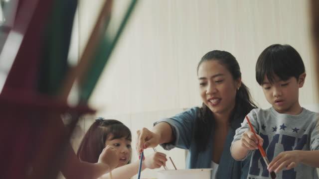 vídeos de stock, filmes e b-roll de asiático professor ensinando aluno na aula de arte - professor de pré escola