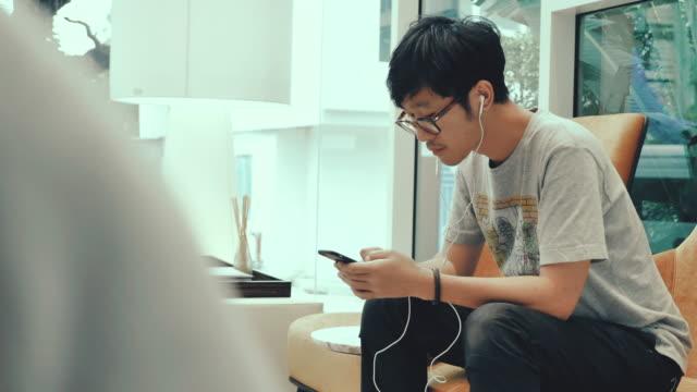 아시아 십 대 소년 휴대 전화에 이어폰으로 음악을 듣고. - 20 29세 스톡 비디오 및 b-롤 화면