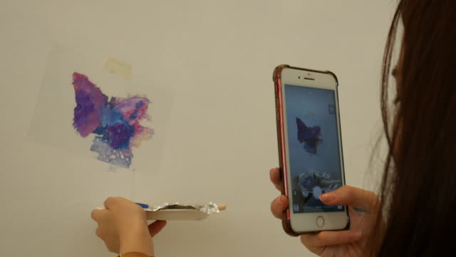 Asian teenage girl using smart phone take a photo for her butterfly acrylic painting on white wall , LGBTQI concept