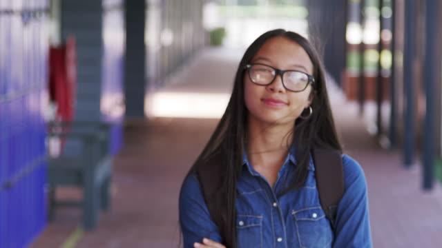 Asian teenage girl walks into focus in high school corridor video