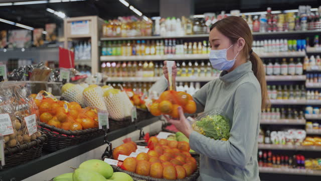 asiatiska tonårsflicka med disponibel medicinsk mask välja grönsakssallad mat i snabbköpet - endast unga kvinnor bildbanksvideor och videomaterial från bakom kulisserna