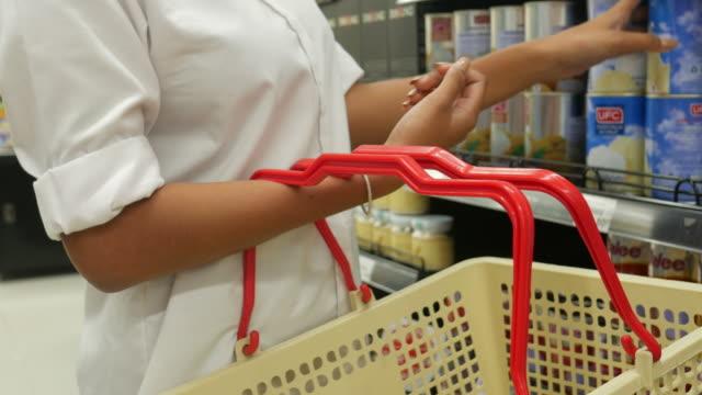 asiatisk tonårs kvinna shopping i stormarknad - dagligvaruhandel, hylla, bakgrund, blurred bildbanksvideor och videomaterial från bakom kulisserna