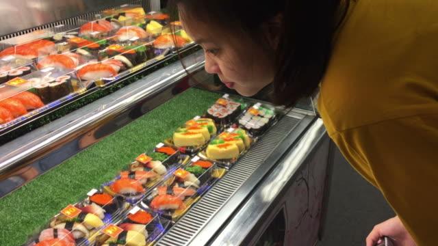 vídeos y material grabado en eventos de stock de mujer adolescente asiática compras en supermercado - sushi