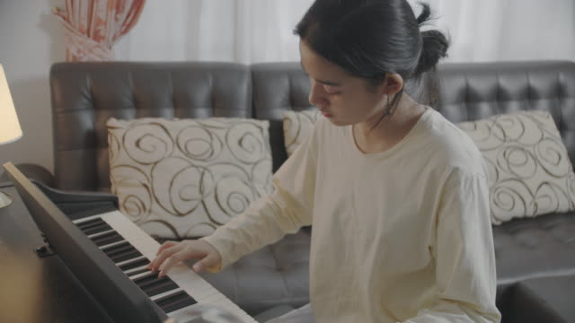 Asian teenager girl playing piano Teleconferencing with music. Playing via video call on internet. Cute girl having fun playing electric piano. Musician teen student teaching online music lesson with her friends on smartphone. Online music class