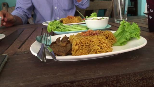 レストランでヤギとアジアのタイ人が食べるビリヤニ ライス ビデオ