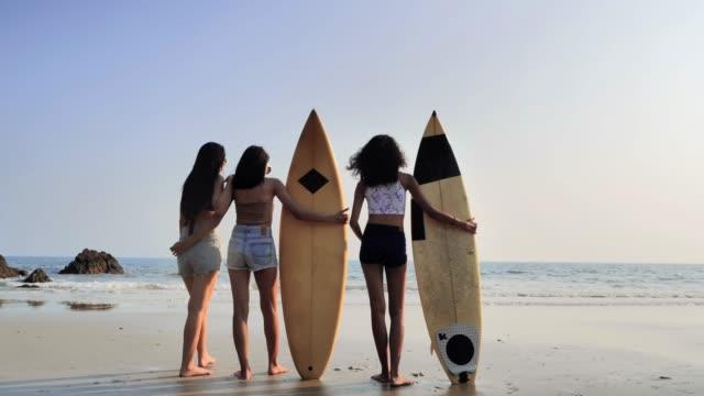 vídeos y material grabado en eventos de stock de tres hermosas mujeres jóvenes surfistas chicas asiáticas en bikini con blanco tablas de surf en una playa. cinemagraphs de deportes - mujer seductora