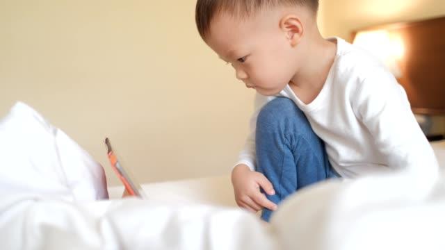 アジア幼児少年デジタル タブレット pc で遊んで - スマホ ベッド点の映像素材/bロール