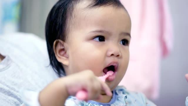 Asian toddler (baby girl) brushing teeth