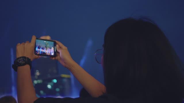 vidéos et rushes de touriste asiatique capturant la vie de ville la nuit dans la ville de bangkok. - prise avec un appareil mobile