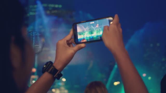 vidéos et rushes de touriste asiatique capturant la vie de ville la nuit dans la ville de bangkok. - photophone