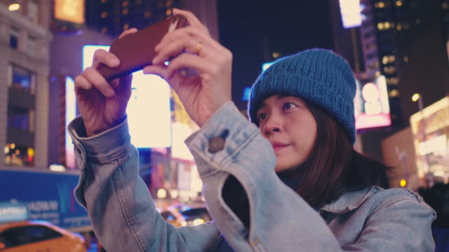 Asian tourist capturing city life at night in Time Square.
