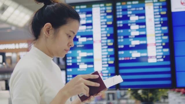 vídeos y material grabado en eventos de stock de asiática turista mujer de cheques y mirando vuelo en llegada a la junta de salida - pasaporte y visa