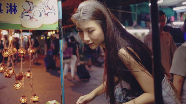 Asian tourist woman enjoying with coconut ice cream at flea markets in Bangkok
