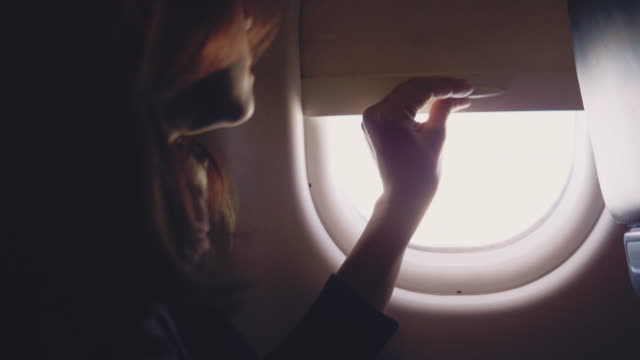 Asian tourist woman open the window on airplane