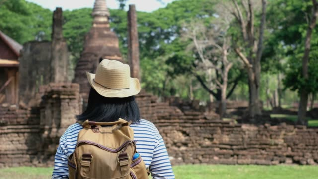 Asian traveler woman walkiing at ancient of pagoda temple thai architecture at Sukhothai,Thailand. Female tourist visiting city concept. Asian traveler woman walkiing at ancient of pagoda temple thai architecture at Sukhothai,Thailand. Female tourist visiting city concept sukhothai stock videos & royalty-free footage