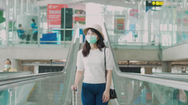 vídeos de stock e filmes b-roll de asian traveler  woman with luggage wearing face mask looking outside terminal in airport standing on escalator go to gate for journey. new normal travel concept. - covid flight