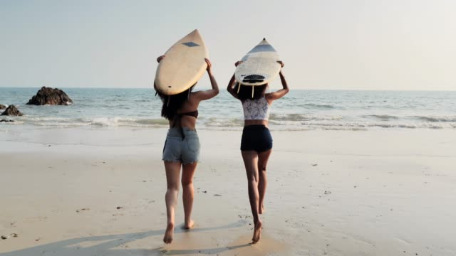 vídeos de stock e filmes b-roll de asian two beautiful young women surfer girls in bikinis with white surfboards at a beach.sports cinemagraphs - rebentação