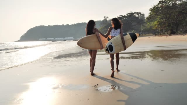 Asian two beautiful young women surfer girls in bikinis with white surfboards at a beach.Sports Cinemagraphs