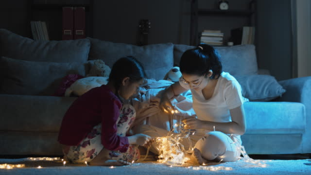 Asian Two sister have fun making light star for decoration on their camping tent  in the living room at home at night time.
