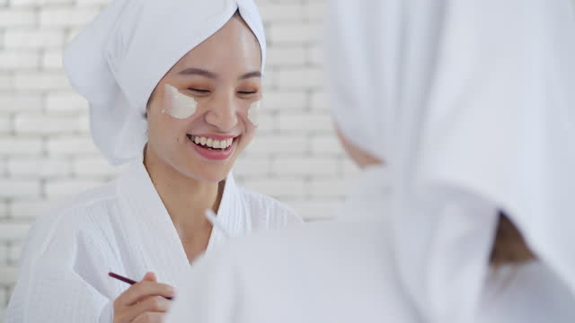 Asian two young women are relaxing spa at home while laughing relaxing together, smiling girls friends having fun.Virtual spa day video