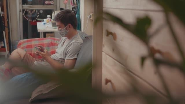 asiatische arbeitslose mann schauen gestresst, versuchen, einen job auf smartphone und tablet wegen der virusprobleme covid-19 zu hause zu finden. - thailändischer abstammung stock-videos und b-roll-filmmaterial