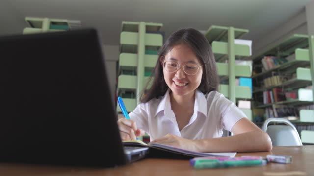 azjatycka studentka czytania książki i pracy z laptopem i inteligentnym telefonem odrabia pracę domową w miejscach publicznych w bibliotece publicznej - uniform filmów i materiałów b-roll
