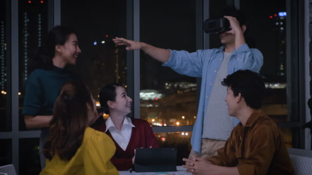 Asian ux developer and ui designer examining virtual reality eyewear with mobile app prototype design at modern office at night with city light.Creative digital development agency
