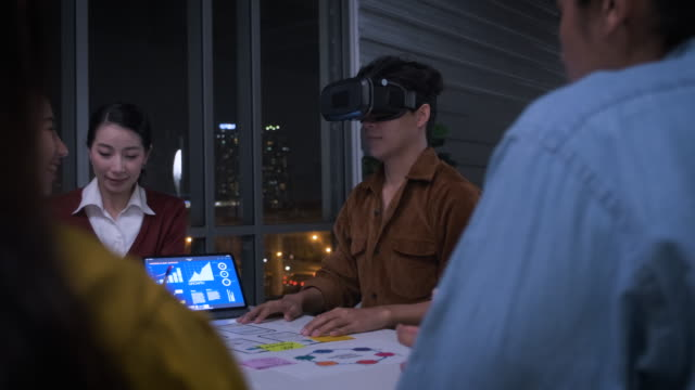 Asian ux developer and ui designer examining virtual reality eyewear with mobile app prototype design at modern office at night with city light.Creative digital development agency.panning