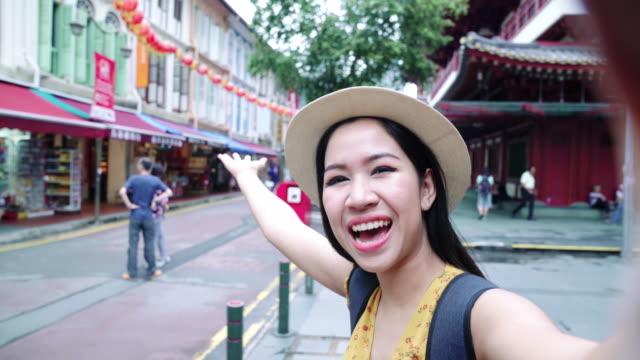 vidéos et rushes de femme asiatique vlogger prenant un selfies à la ville de chine à singapour. - interview