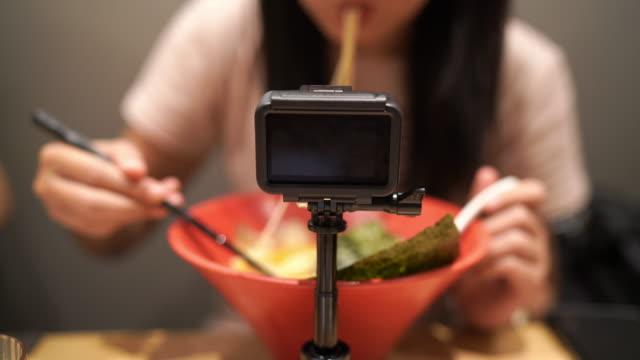 vídeos de stock, filmes e b-roll de asiático vlogger mulher vlogging ou selfie ela mesma comendo japonês ramen noodle - blogar