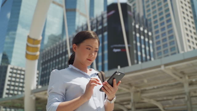 Asian walking and talking a smartphone at the city slow motion video