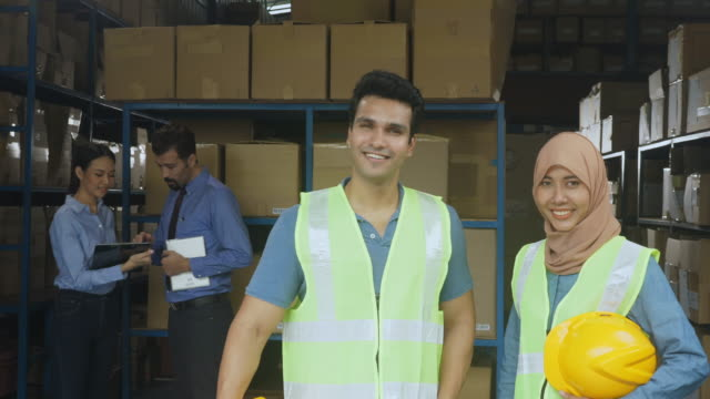 Asian warehouse worker standing and smiling in front of storehouse.Muslim staff coworkers holding helmet