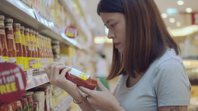 asiatische ehefrau im lebensmittelgeschäft - etikett stock-videos und b-roll-filmmaterial