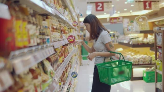 vídeos y material grabado en eventos de stock de esposa asiática en la tienda de comestibles - eventos de etiqueta