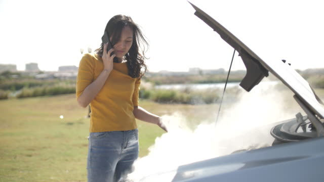 Asian with Woman Car broken down on road opening the radiator bonnet Car and see engines Car,Broken,Moving Down, Asian Woman opening the radiator bonnet Car and see engines and using Smart phone while looking at broken down car on street. Smoking car engine breaking stock videos & royalty-free footage