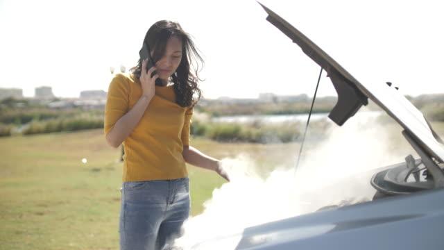 vídeos de stock, filmes e b-roll de asiático com carro da mulher quebrado para baixo na estrada que abre o carro da capota do radiador e vê motores - mover para baixo