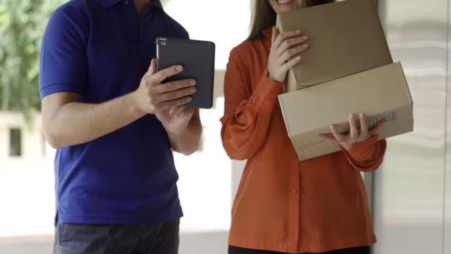 vídeos de stock, filmes e b-roll de mulher asiática e entregador que lhe dá caixa de papelão pacote postal - correio correspondência