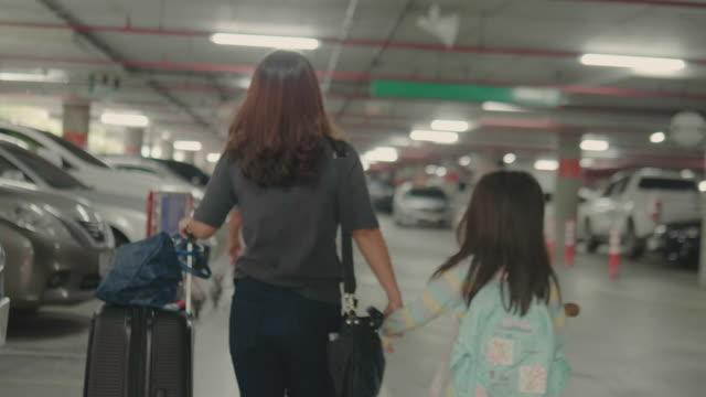 stockvideo's en b-roll-footage met aziatische vrouw of het meisje met de koffer op parkeerplaats. - parking