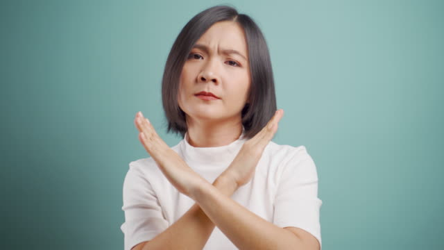 Asian woman  angry and showing arms crossed make stop sign and standing isolated over blue background. Health care concepts. 4k video. video