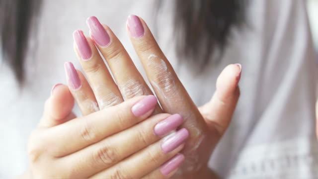 Asian woman applies cream on her beautiful hands closeup video