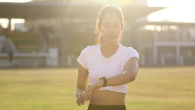 Asian Woman applying and spraying sunscreen cream on skin before run. Sports and healthy concept - vídeo