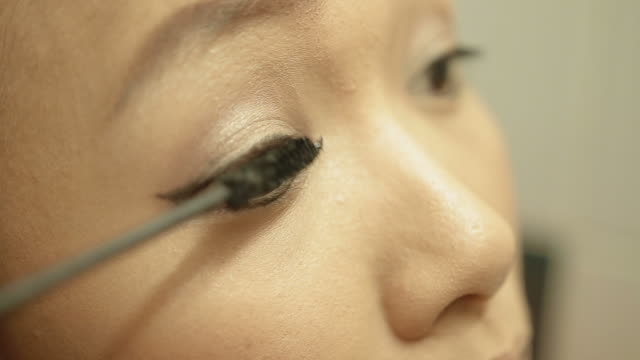 Asian woman applying eye make up Asian woman applying mascara on her eyelash by herself.flat picture profile for color grading.close up shot mascara stock videos & royalty-free footage