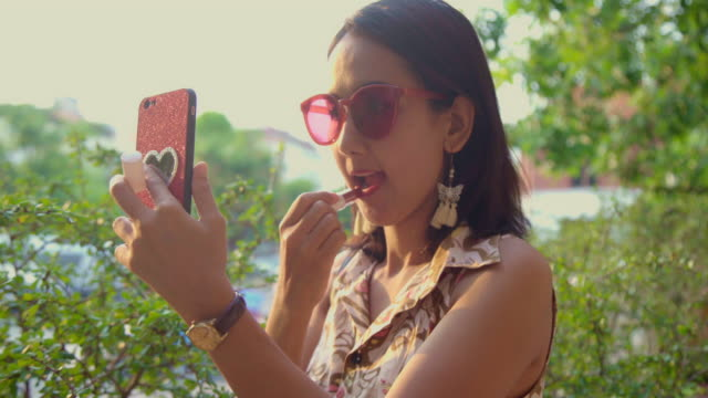 Asian Woman applying Red Lipstick and Looking a Makeup at her Mobile Phone. Beautiful Woman Portraits with Fashionista Look. Asian Woman applying Red Lipstick and Looking a Makeup at her Mobile Phone. Beautiful Woman Portraits with Fashionista Look. red lipstick stock videos & royalty-free footage