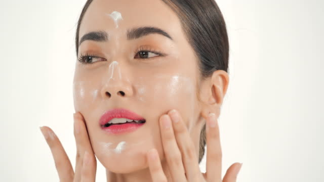 Asian woman applying skin face cream on white background. Beautiful woman touching her face with happy emotion.Expressive facial expressions.Cosmetology and Spa.Beauty Face.Video: Diverse Portraits - vídeo