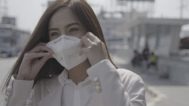 asian woman are going to work.she wears n95 mask.prevent pm2.5 dust and smog - mask filmów i materiałów b-roll